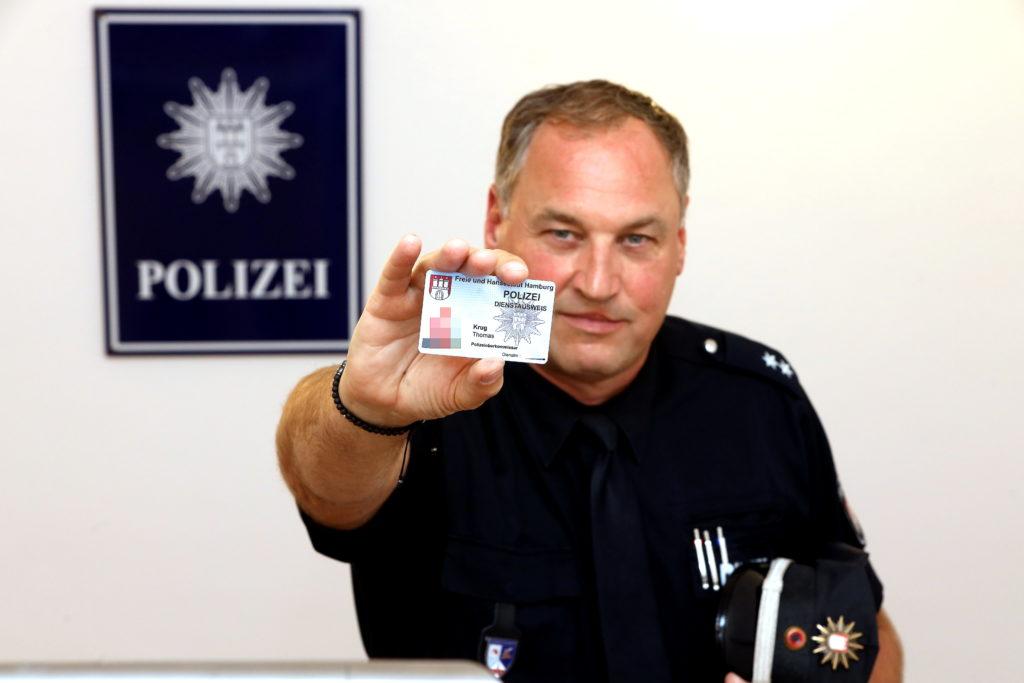 Polizist Thomas Krug zeigt seinen Dienstausweis