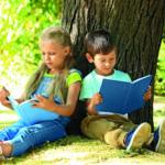 Lesende Kinder vor einem Baum