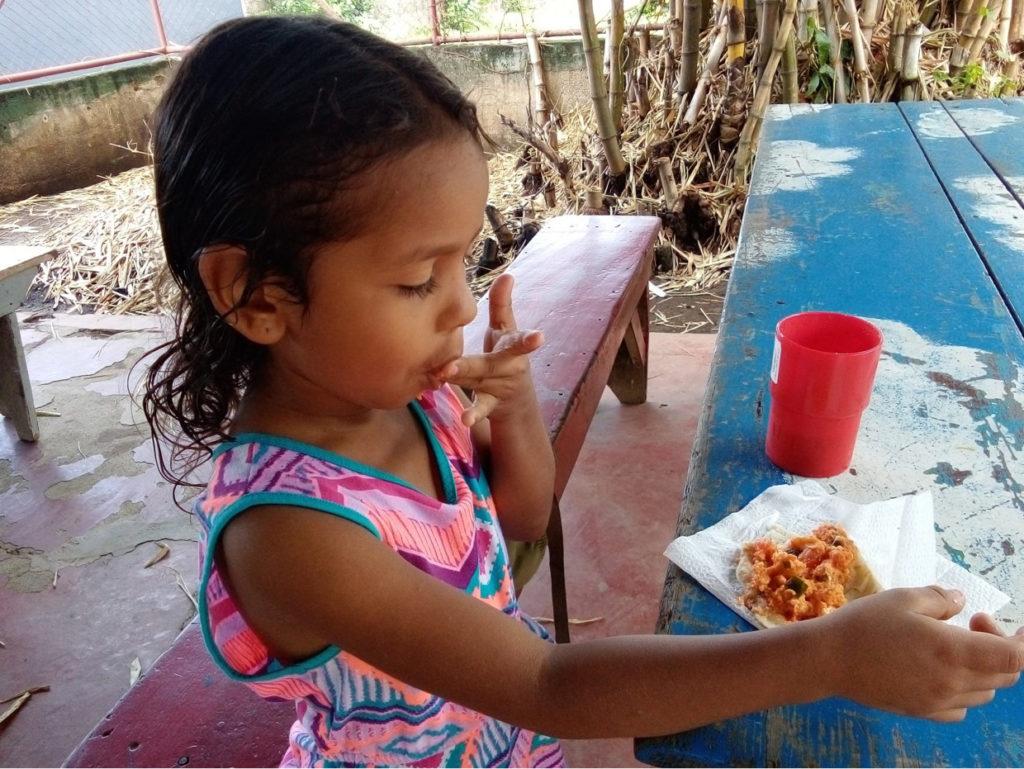 Kind isst seine Schulmahlzeit in Nicaragua