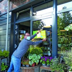 Herr Haecks hängt das Corona-Plakat an sein Schaufenster