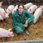 Ulrike SchreUlrike Schreiber umgeben von schweinischen Glücksbringern auf dem Bio-Gut Wulksfelde