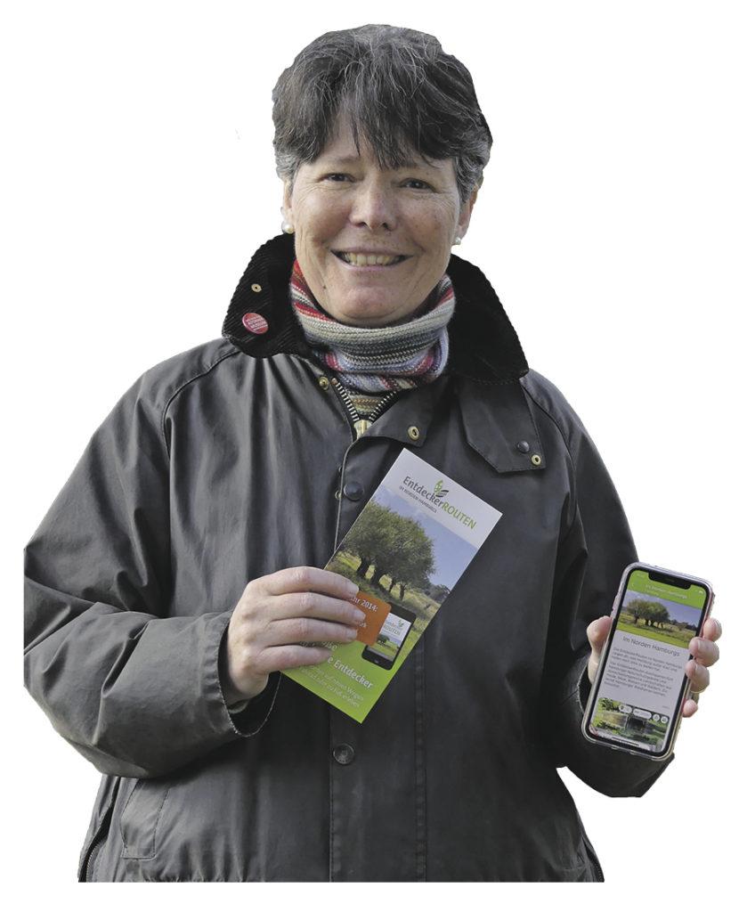 Dr. Susan Müller-Wusterwitz mit Prospekt und Handy ihrer Entdeckertour-App