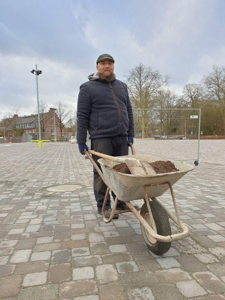 Mann mit Schubkarre auf dem Volksdorfer Marktplatz