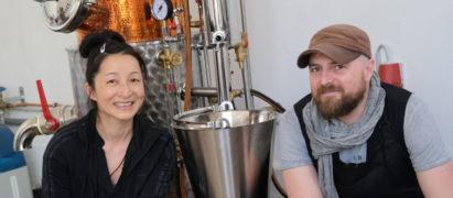 Yuka Suzuki und Hauke Günther vor ihrer Destillieranlage. Dreimal täglich wird die Brennblase angeheizt.Fotos: Marius Leweke