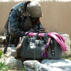 Obdachloser mit Habe sitzt vor einer Mauer