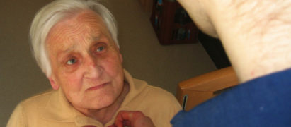 Pfleger hilft altem Menschen beim Anziehen