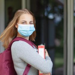 Mädchen mit Maske und Ordner vor Schule
