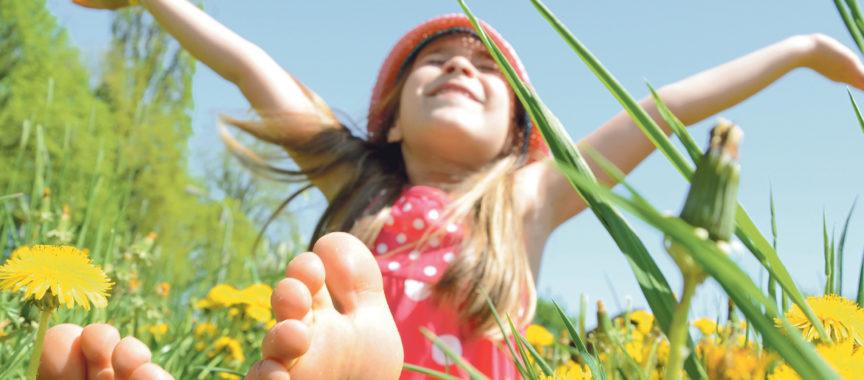 Kind sitzt in der Blumenwiese