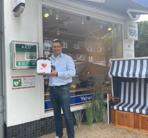 Geschäftsführer Vincent Paul Menken zeigt das frei zugängige Gerät vor dem Ladengeschäft von Menken und Schlief Immobilien in Klein Borstel.