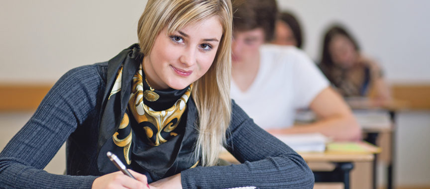 Schülerin beim Lernen, sitzt an ihrem Schreibtisch
