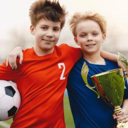 Fussball-Jungs mit Ball und Pokal für Sport Sonderseiten