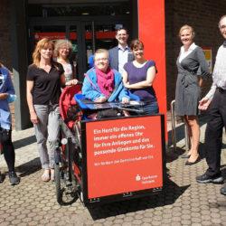 Übergabe der Rollstuhl Rikscha vor der Sparkasse Stormarn